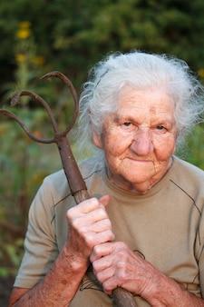 Portrait d'une vieille femme aux cheveux gris tenant une fourche rouillée