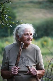Portrait d'une vieille femme marchant dans une prairie herbeuse