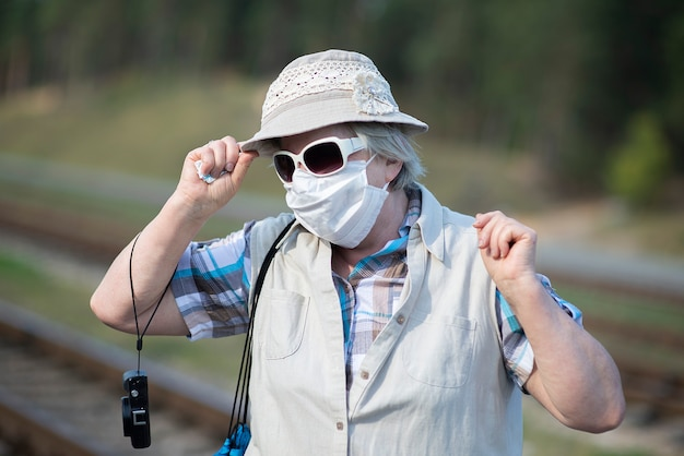 Portrait de vieille femme senior avec masque médical sur le visage, chapeau, lunettes de soleil et appareil photo