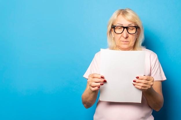 Portrait d'une vieille femme sympathique dans un t-shirt décontracté et des lunettes tenant une feuille de papier dans ses mains et la regardant sur un mur bleu isolé. visage émotionnel. lettre de concept, avis