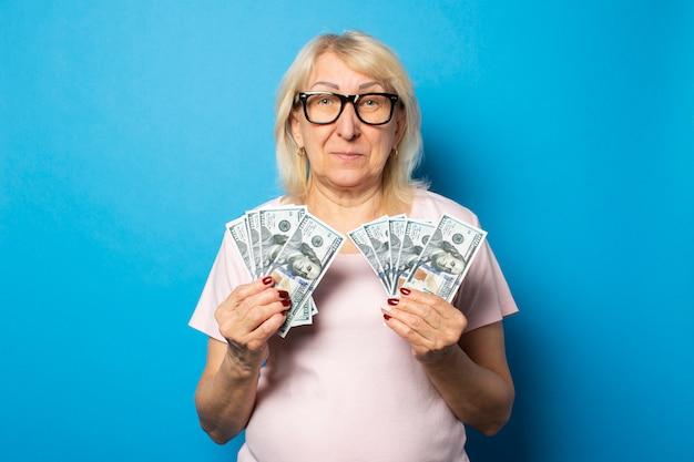Portrait d'une vieille femme sympathique en t-shirt décontracté et lunettes tenant de l'argent dans ses mains sur un mur bleu isolé. visage émotionnel. concept richesse, victoire, crédit, pension