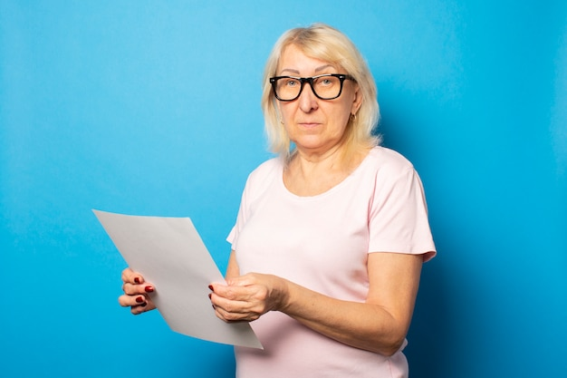 Portrait d'une vieille femme sympathique en t-shirt décontracté et lunettes tenant une feuille de papier dans ses mains sur un mur bleu isolé. visage émotionnel. lettre de concept, avis