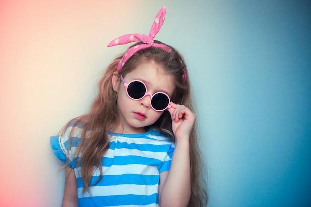 Portrait vintage de fille à lunettes de soleil et arc