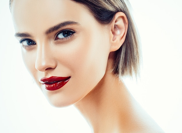 Portrait de visage de femme de beauté. beau modèle fille avec des lèvres de couleur perfect fresh clean skin rouge violet. blonde brune cheveux courts concept de jeunesse et de soins de la peau. isolé sur fond blanc