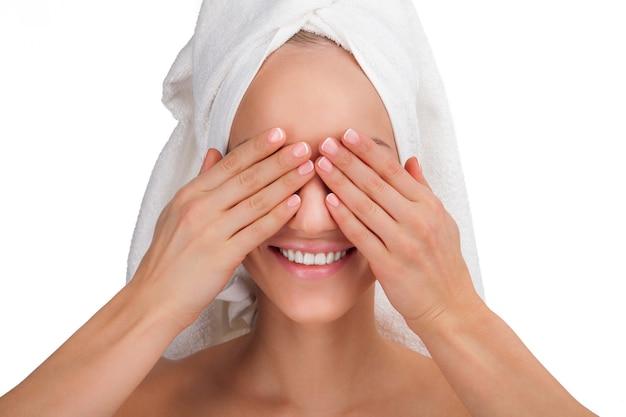Portrait de visage de femme de beauté. jeune fille souriante dans une serviette ferme les yeux à la main.