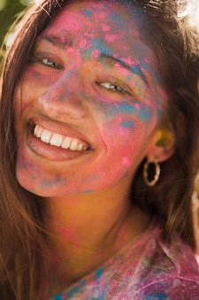 Portrait d'un visage de femme souriant recouvert de couleur holi