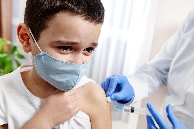 Portrait de visage d'un garçon inquiet effrayé portant un masque médical, les mains du médecin le vaccinant