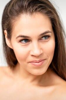 Portrait de visage de jeune femme de race blanche aux épaules nues et maquillage naturel sur mur blanc