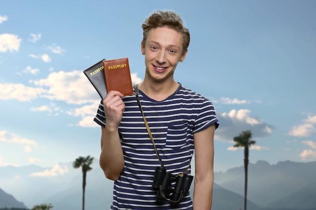 Portrait d'un voyageur adolescent souriant détenant des passeports. ciel bleu en arrière-plan.