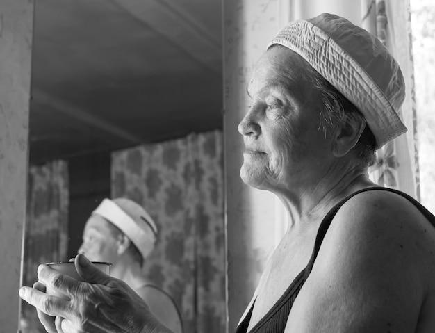 Portrait de vraie femme fatiguée souriante agricultrice après le travail se reposant à la maison et regardant par la fenêtre