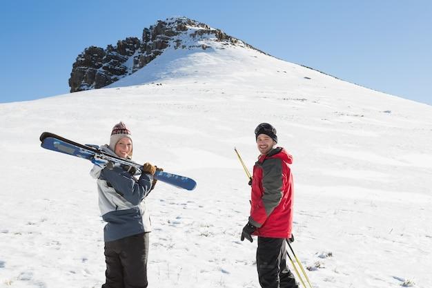 Portrait de vue arrière d'un couple souriant avec des planches de ski sur la neige