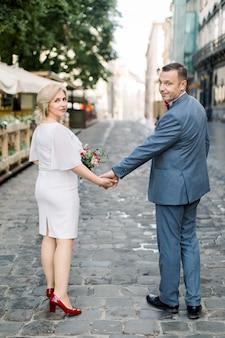 Portrait de vue arrière de tout le corps d'un couple heureux et mature, portant des vêtements élégants de luxe, marchant dans la rue de la ville, ayant une date ou une célébration d'anniversaire de mariage