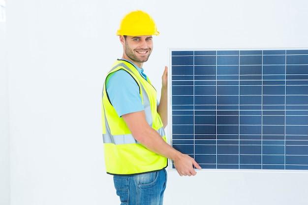 Portrait de vue de côté de l'architecte heureux holding panneau solaire sur fond blanc