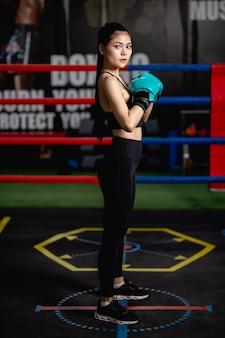 Portrait vue de côté jeune jolie femme en gants de boxe pose debout avec un corps parfait sur toile dans une salle de fitness, cours de boxe d'entraînement pour fille en bonne santé,