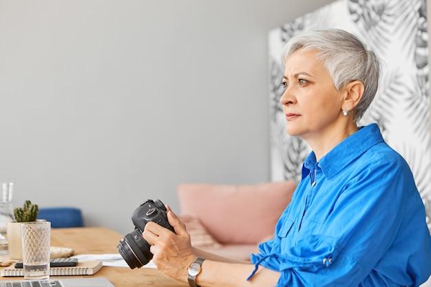 Portrait de vue de côté d'une journaliste sérieuse et élégante d'âge moyen travaillant à distance du bureau à domicile, assise à son bureau à domicile avec appareil photo reflex numérique. personnes, profession, créativité, âge et technologie