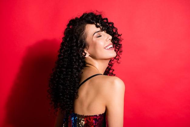 Portrait de vue de côté de profil en gros plan d'une magnifique fille aux cheveux ondulés rêveuse et gaie s'amusant isolée sur fond de couleur rouge vif