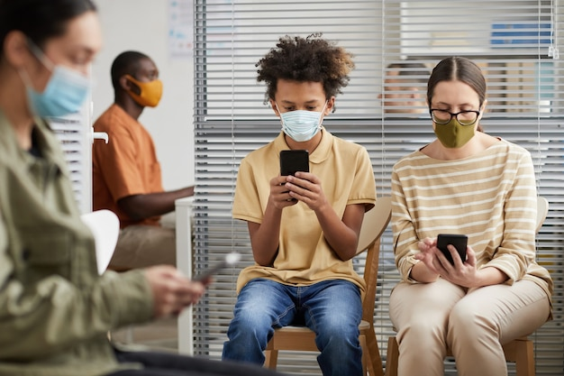 Portrait vue de face d'un groupe multiethnique de personnes utilisant des smartphones en faisant la queue à la clinique médicale, toutes portant des masques
