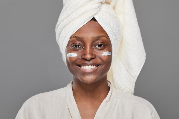 Portrait de vue de face minimal d'une belle femme afro-américaine profitant de soins de la peau et regardant la caméra avec une crème pour le visage ou une crème hydratante, espace pour copie