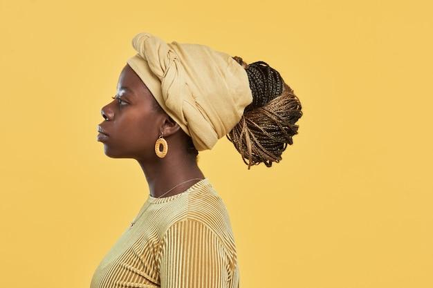 Portrait de vue latérale minimale d'une jeune femme afro-américaine portant un foulard et des bijoux ethniques...