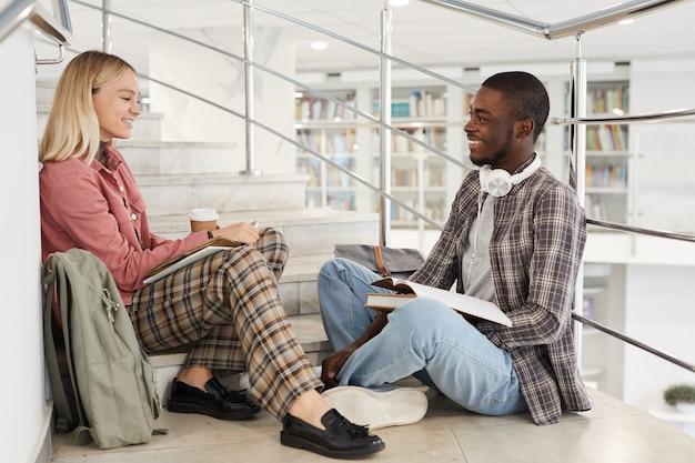 Portrait de vue latérale sur toute la longueur de deux étudiants discutant alors qu'ils étaient assis sur les escaliers au collège,
