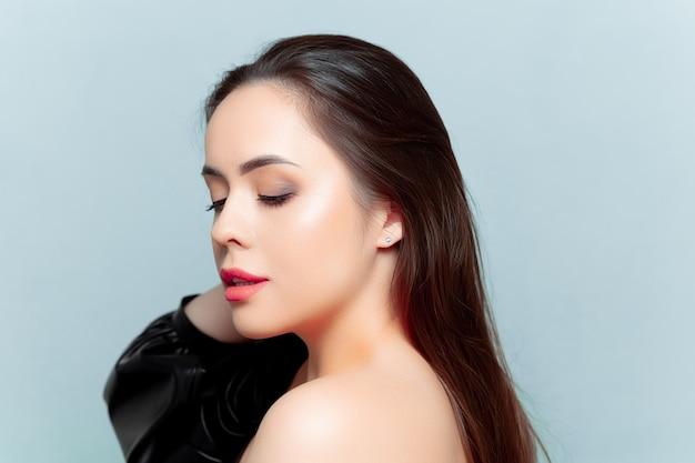 Portraits d'un beau modèle brune qui se tient sur le côté et redresse ses cheveux