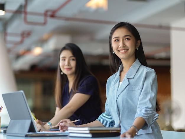 Portraits de deux femmes d'affaires côte à côte dans la salle de réunion