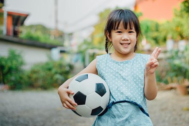 Les portraits d'un enfant aiment jouer au football pour l'exercice.