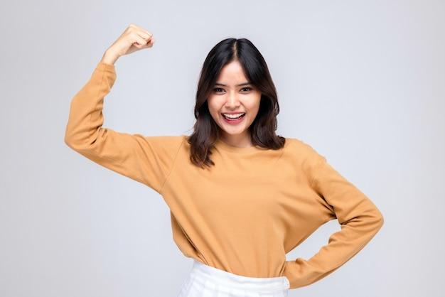 Portraits de jeunes femmes asiatiques. levez les bras. avec un visage souriant joyeusement, une belle femme avec un sentiment de confiance en soi, a l'air bien, heureuse sur un fond gris.