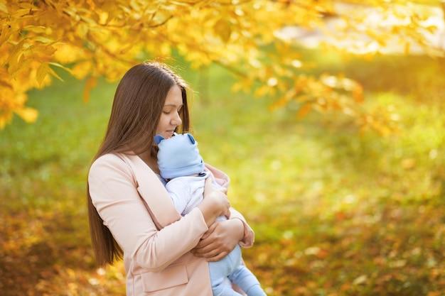 Portraits de maman et bébé dans le parc d'automne, maman embrasse bébé