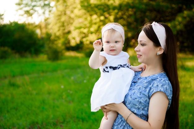 Portret de l'heureuse mère avec sa fille jouant sur l'herbe dans le parc le soir