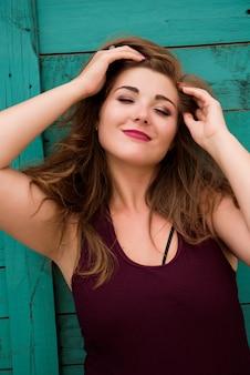 Portret d'un modèle fille plus la taille sur l'arrière-plan d'un mur vert