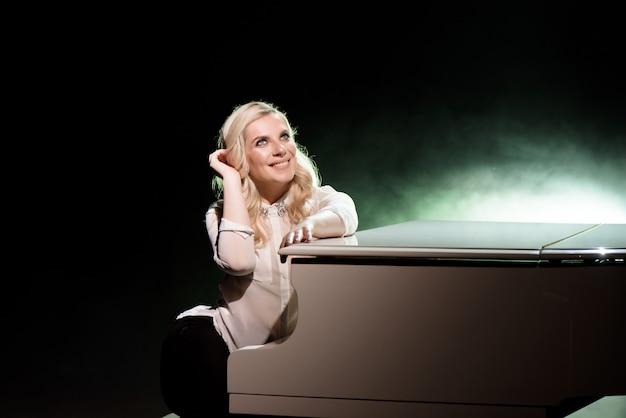 Portret de pianiste posant près d'un piano blanc sur la scène dans le faisceau de lumière.