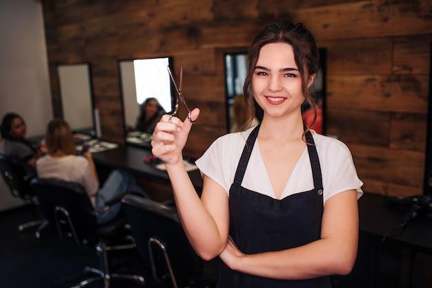 Portret de sourire belle femme coiffeur avec tablier noir regardant la caméra