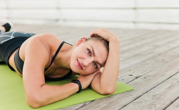 Portret young fit woman in sportswear allongé sur un tapis sur une terrasse en bois sur la plage.