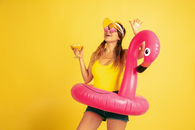 Posant en anneau de plage avec cocktail. portrait de femme caucasienne sur fond jaune. beau modèle féminin en casquette. concept d'émotions humaines, expression faciale, ventes, publicité. l'été, les voyages, la station balnéaire.