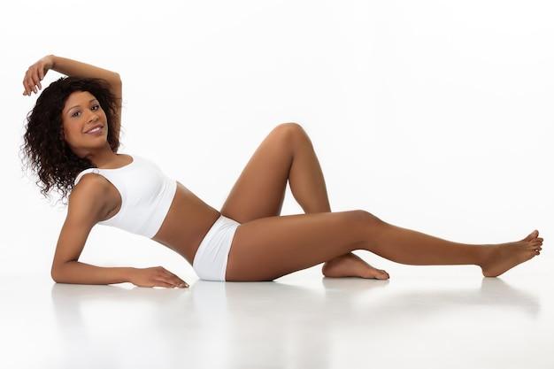Posant confiant, s'aime. slim femme bronzée sur fond de studio blanc. modèle afro-américain à la forme et à la peau soignées. beauté, soins personnels, remise en forme, concept minceur. soins de santé.