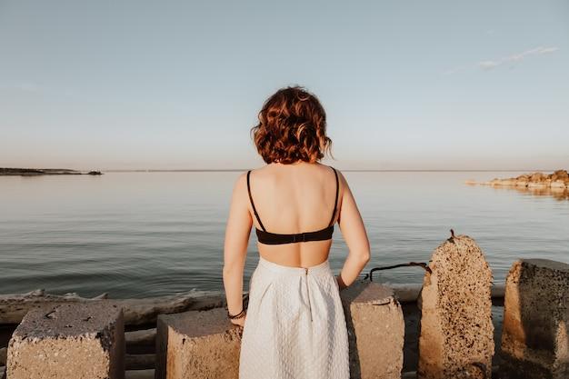 Posant la femme dans la nature. jeune femme dans des vêtements élégants. haut et jupe blanche assis sur des pierres sur fond de mer.