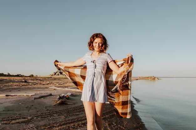 Posant la femme dans la nature. jeune femme en robe bleue avec un plaid posant et marchant