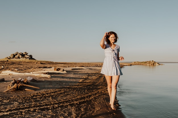 Posant la femme dans la nature. jeune femme en robe bleue posant et marchant