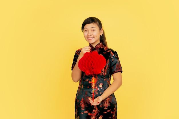 Posant avec lanterne, souriant, invitant. joyeux nouvel an chinois. portrait de jeune fille asiatique sur fond jaune. copyspace.