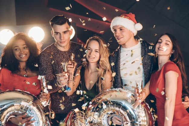 Posant pour la photo. photo de la compagnie de quatre amis ayant la fête avec de l'alcool