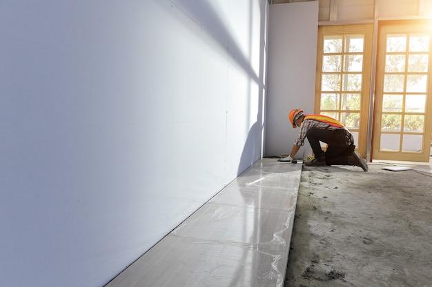 Pose de carreaux de céramique.amélioration des carreaux à domicile - bricoleur avec niveau.carreleur travaille avec le revêtement de sol