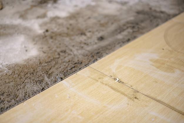 Pose de carreaux de sol en céramique avec des croix en plastique pour le nivellement