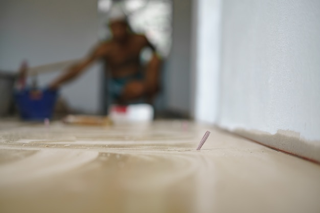 Pose de carreaux de sol en céramique avec un morceau de papier pour niveler un espace