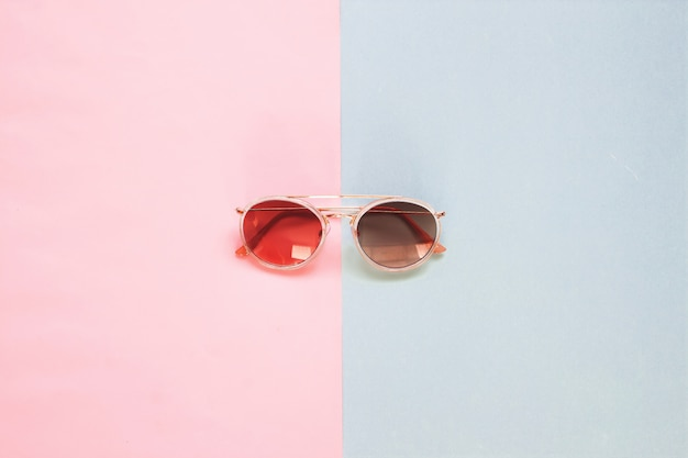 Pose créative de lunettes de soleil à la mode sur fond de ton de couleur pastel.