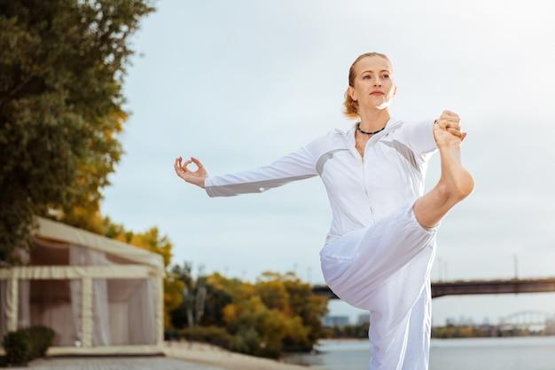 Pose équilibrée. femme calme et confiante debout sur une jambe