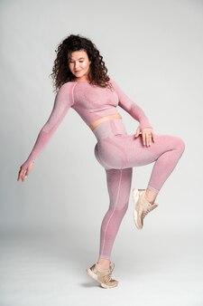 Pose intéressante. vue sur toute la longueur de la femme brune bouclée debout sur une jambe et regardant vers le bas tout en posant sur le fond du mur blanc