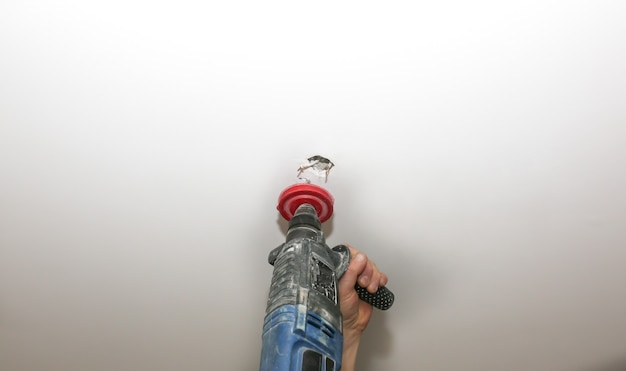 Pose de la lampe. homme faisant un trou dans le plafond avec une perceuse électrique. restauration à l'intérieur. travail d'entretien.