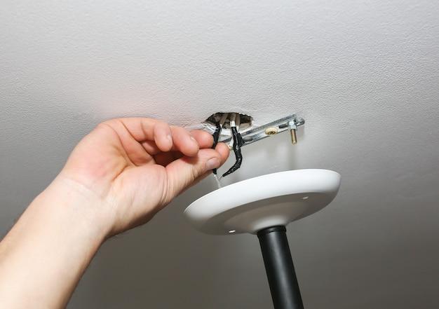 Pose de la lampe. homme tenant la construction. restauration à l'intérieur. travail d'entretien.