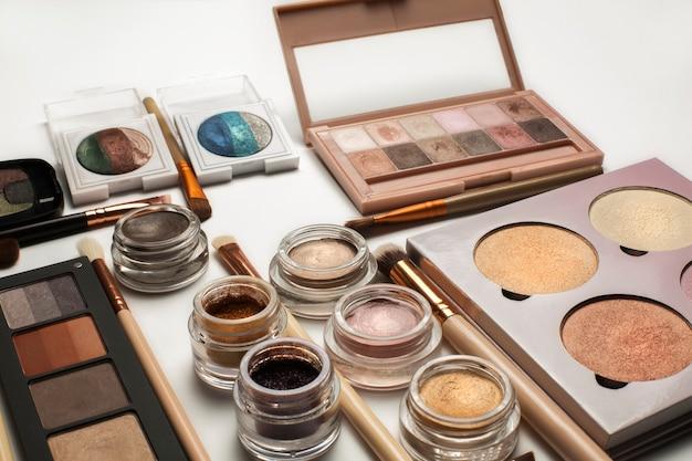 Pose à plat de palettes de fards à paupières, pinceaux cosmétiques et pigments chatoyants